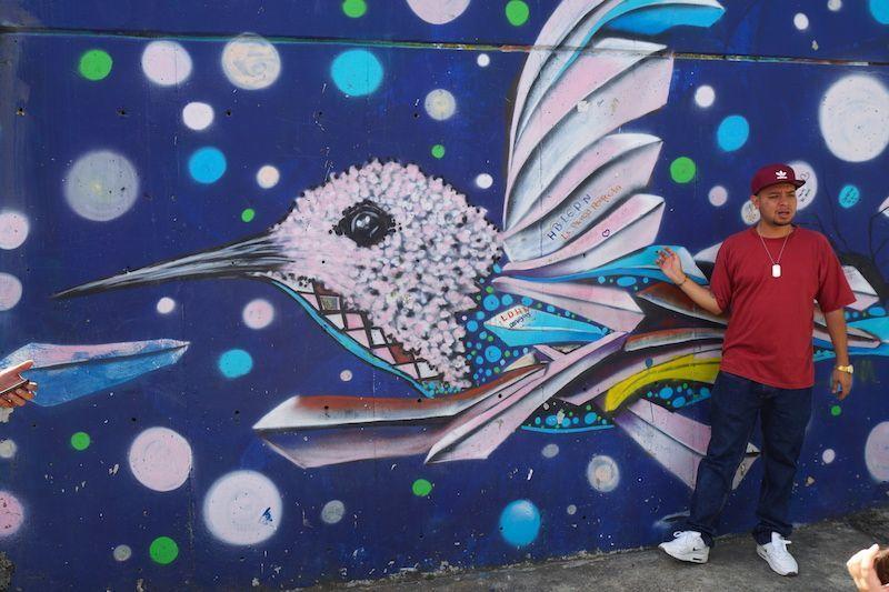 Daniel, nuestro guía de Casa Kolacho, frente a una de las obras en Comuna 13